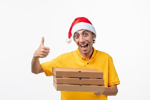 Corriere maschio vista frontale con scatole per pizza su un lavoro di consegna uniforme muro bianco