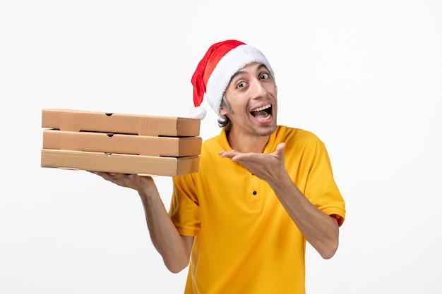Corriere maschio vista frontale con scatole per pizza sul servizio di consegna uniforme muro bianco