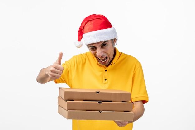 Corriere maschio di vista frontale con scatole di pizza sul nuovo anno uniforme di servizio del lavoro della parete bianca