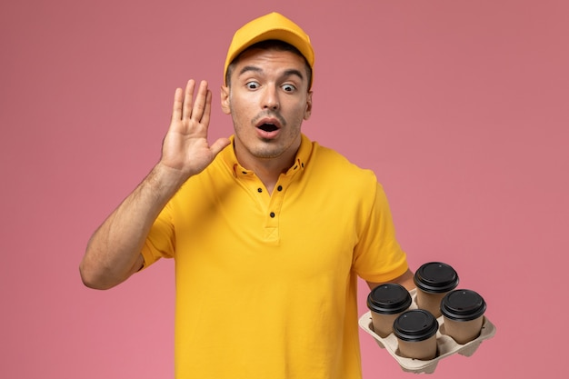 Front view male courier in yellow uniform calling out and holding delivery coffee cups on the pink desk