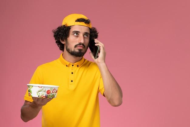 Corriere maschio di vista frontale nella ciotola di consegna del capo uniforme gialla sulle sue mani mentre parla al telefono su sfondo rosa chiaro.