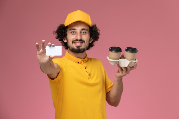 Front view male courier in yellow uniform and cape holding brown delivery coffee cups and card on light pink wall