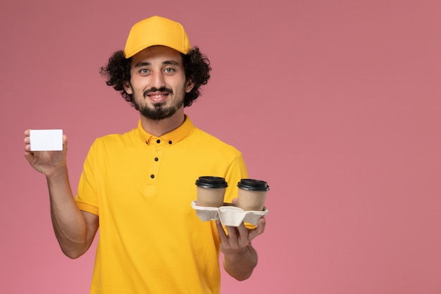 Front view male courier in yellow uniform and cape holding brown delivery coffee cups and card on pink wall