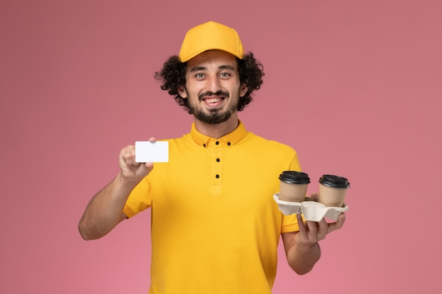 Front view male courier in yellow uniform and cape holding brown delivery coffee cups and card on the pink wall