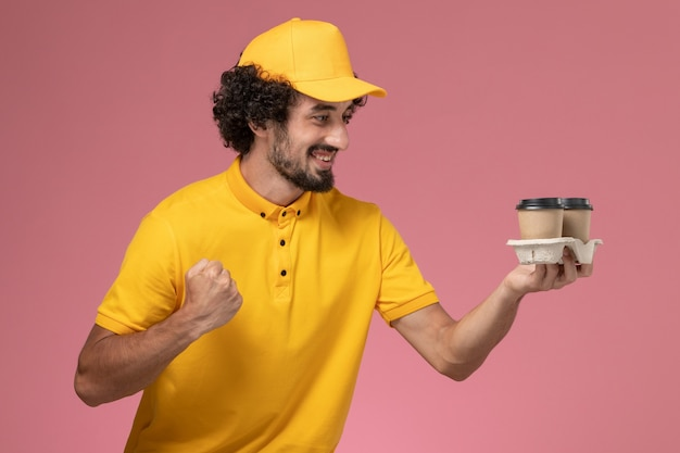 Front view male courier in yellow uniform and cape holding brown delivery coffee cups and cheering on pink wall