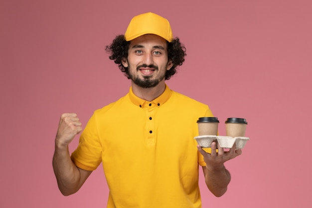 Front view male courier in yellow uniform and cape holding brown delivery coffee cups cheering on pink wall