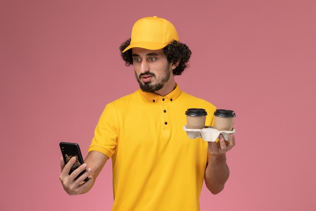 Front view male courier in yellow uniform and cape holding brown delivery coffee cups and his phone on pink wall