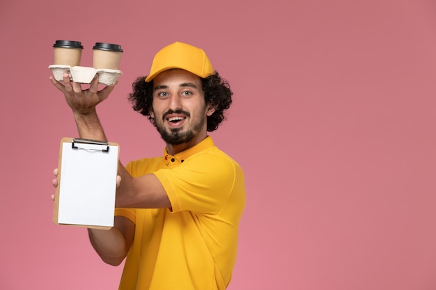 Front view male courier in yellow uniform and cape holding brown delivery coffee cups and notepad on light pink wall