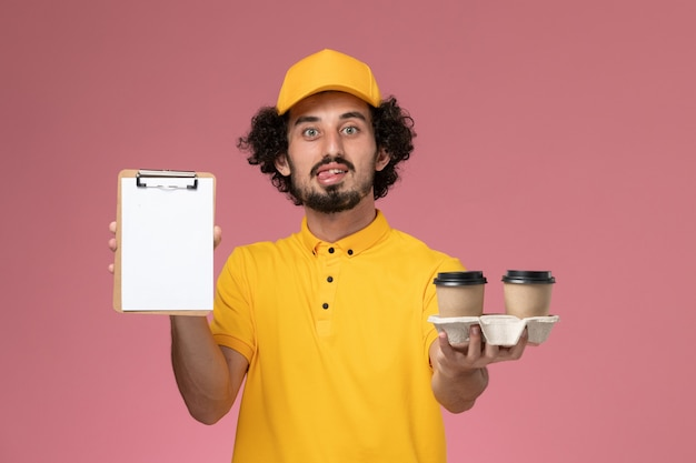 Front view male courier in yellow uniform and cape holding brown delivery coffee cups and notepad on pink wall