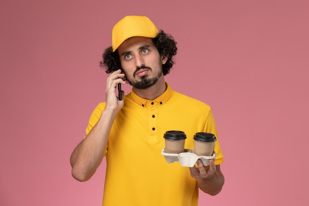 Front view male courier in yellow uniform and cape holding brown delivery coffee cups and talking on the phone on the pink wall