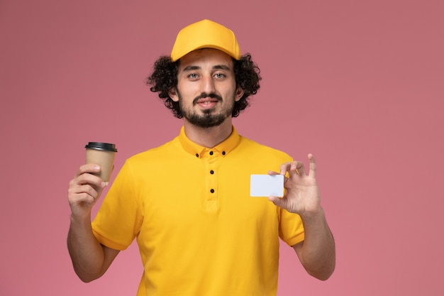 Front view male courier in yellow uniform and cape holding delivery coffee cup and card on pink wall