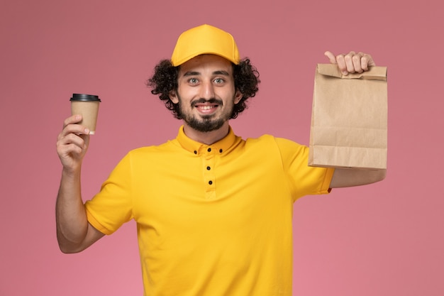 Corriere maschio di vista frontale in uniforme gialla e mantello che tiene la tazza di caffè di consegna e il pacchetto di cibo sul lavoratore dell'azienda di servizio di lavoro uniforme da scrivania rosa