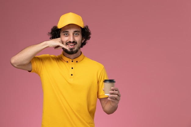 Front view male courier in yellow uniform and cape holding delivery coffee cup on light pink wall