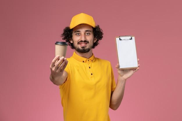 Corriere maschio di vista frontale in uniforme gialla e tazza di caffè di consegna della tenuta del capo e blocco note sulla parete rosa
