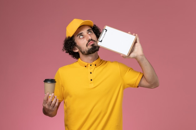 Front view male courier in yellow uniform and cape holding delivery coffee cup and notepad thinking on pink wall