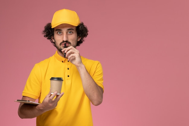 Front view male courier in yellow uniform and cape holding delivery coffee cup pen and notepad thinking on pink wall