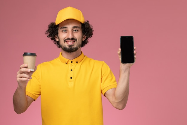 Front view male courier in yellow uniform and cape holding delivery coffee cup and phone on pink wall