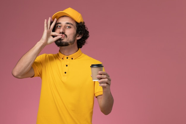 Front view male courier in yellow uniform and cape holding delivery coffee cup on the pink wall