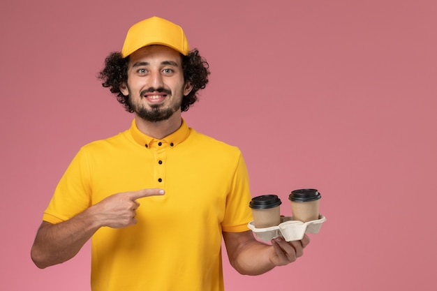 Front view male courier in yellow uniform and cape holding delivery coffee cups on the pink wall