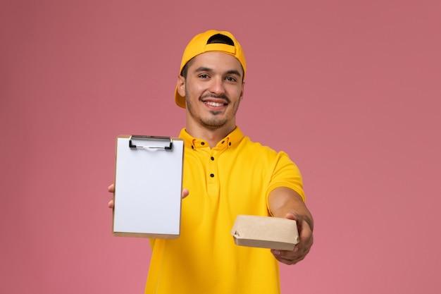 Corriere maschio di vista frontale in uniforme gialla e mantello che tiene poco pacchetto di cibo di consegna e blocco note sullo sfondo rosa.