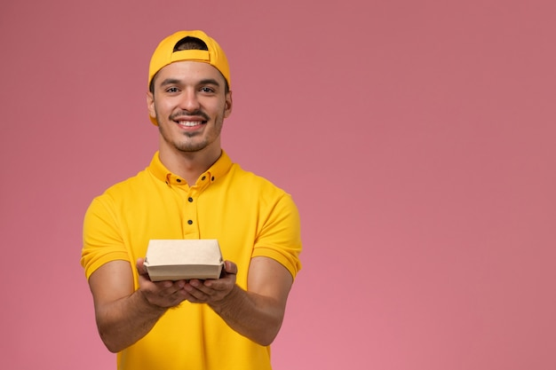 Front view male courier in yellow uniform and cape holding little delivery food package on the pink background.