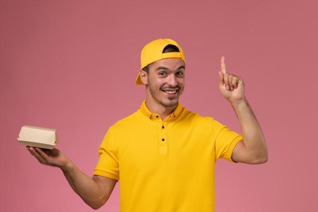 Corriere maschio di vista frontale in uniforme gialla e mantello che tiene piccolo pacchetto di cibo di consegna e sorridente su sfondo rosa chiaro.