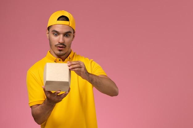 Corriere maschio di vista frontale in uniforme gialla e mantello che tiene e apre piccoli pacchetti di cibo di consegna sullo sfondo rosa.