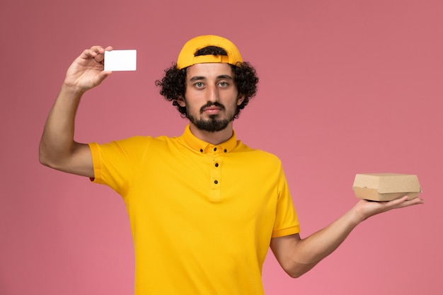Front view male courier in yellow uniform and cape with card and little delivery food package on his hands on the light pink background.