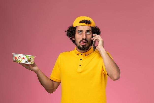 Corriere maschio di vista frontale in mantello uniforme giallo con ciotola di consegna sulle sue mani parlando al telefono sullo sfondo rosa chiaro.