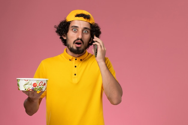 Corriere maschio vista frontale in mantello giallo uniforme con ciotola di consegna sulle mani mentre parla al telefono su sfondo rosa chiaro.