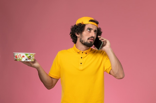 Front view male courier in yellow uniform cape with delivery bowl and smartphone on his hands on light-pink background.