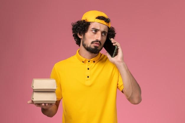 Corriere maschio vista frontale in mantello giallo uniforme con pacchi di cibo sulle mani parlando al telefono su sfondo rosa chiaro.