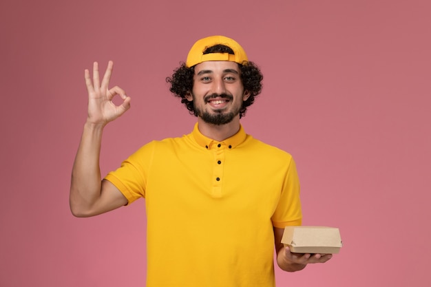 Front view male courier in yellow uniform and cape with little delivery food package on his hands smiling on the pink background.