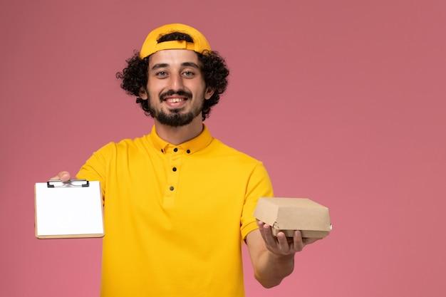 Corriere maschio vista frontale in uniforme gialla e mantello con blocco note e piccolo pacchetto di cibo di consegna sulle sue mani sullo sfondo rosa chiaro.