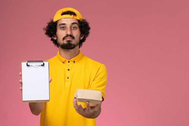 Front view male courier in yellow uniform and cape with notepad and little delivery food package on his hands on pink background.
