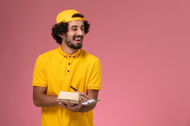 Front view male courier in yellow uniform and cape with notepad and little delivery food package on his hands and writing notes on pink background.