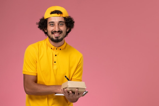 Front view male courier in yellow uniform and cape with notepad and little delivery food package on his hands writing notes on pink background.