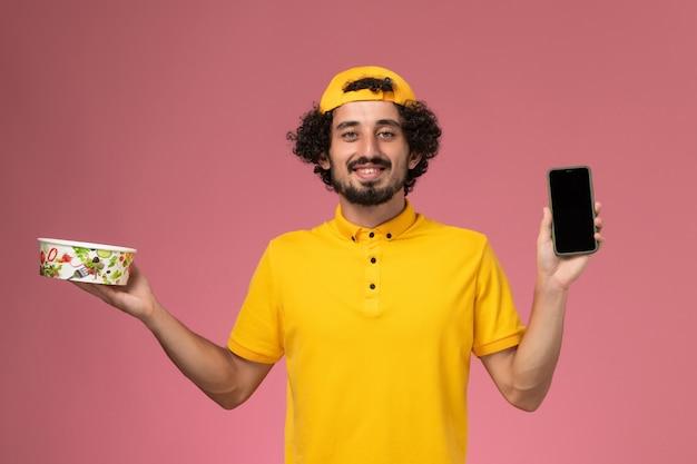 Corriere maschio vista frontale in mantello giallo uniforme con telefono e ciotola di consegna sulle sue mani su sfondo rosa chiaro.
