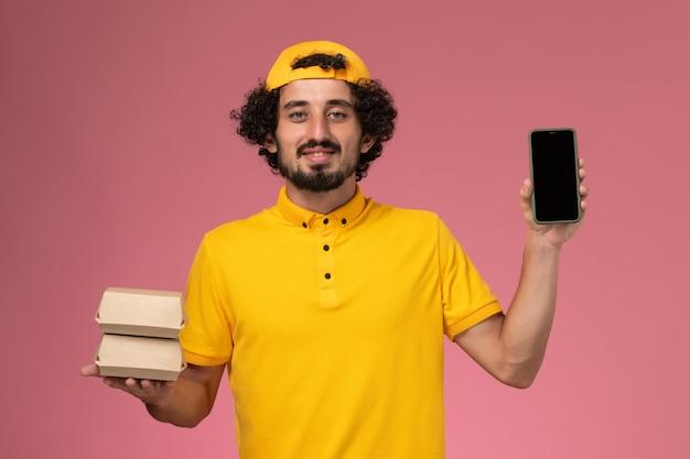 Corriere maschio vista frontale in mantello giallo uniforme con pacchetti di telefono e cibo sulle mani su sfondo rosa chiaro.