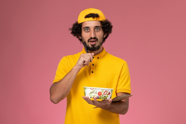 Front view male courier in yellow uniform cape with round delivery bowl on his hands writing notes on the pink background.