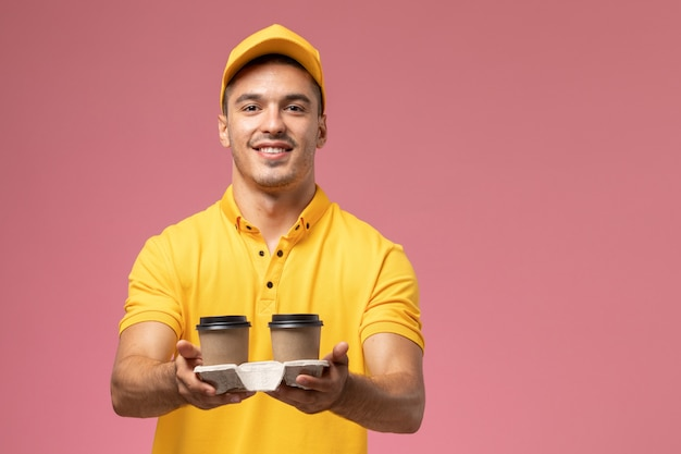 Front view male courier in yellow uniform delivering delivery coffee cups on the light-pink background