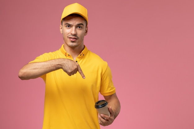 Front view male courier in yellow uniform holding brown coffee delivery cup on the pink background