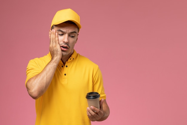 Front view male courier in yellow uniform holding brown coffee delivery cup on the pink desk