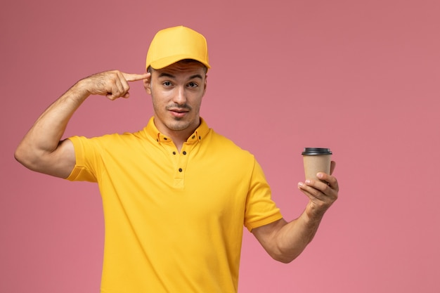 Front view male courier in yellow uniform holding brown coffee delivery cup touching his temple on the pink desk