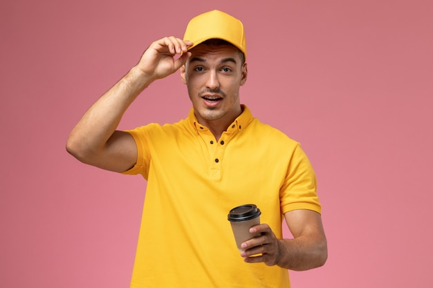 Front view male courier in yellow uniform holding brown delivery coffee cup on the pink background