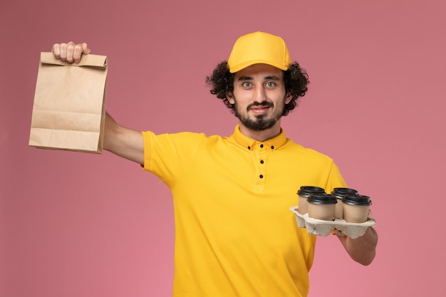 Front view male courier in yellow uniform holding brown delivery coffee cups and food package on the pink wall