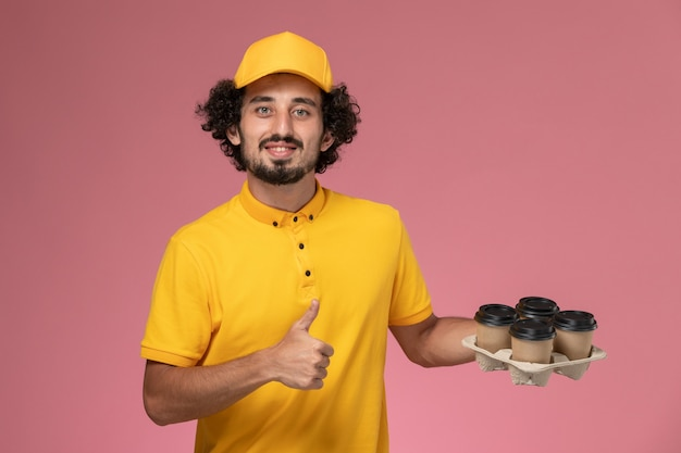 Front view male courier in yellow uniform holding brown delivery coffee cups on pink wall