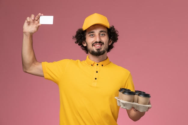 Front view male courier in yellow uniform holding brown delivery coffee cups and white card on light-pink wall