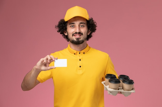 Front view male courier in yellow uniform holding brown delivery coffee cups and white card on pink wall