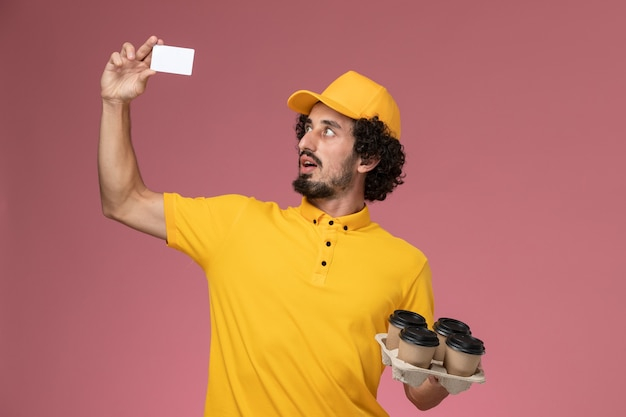 Front view male courier in yellow uniform holding brown delivery coffee cups and white card on the pink wall